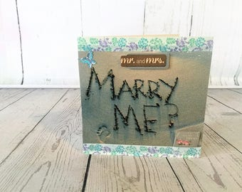 Enchanting marry me card, with marry me written in the sand at a beach.