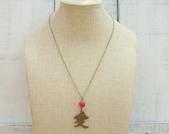 Asian inspired love pendant necklace in antique brass with wire-wrapped pink Tagua seed bead accent // Gift for her