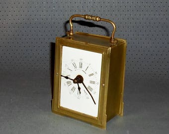 Antique travel alarm clock in brass case with enamelled dial and alarm function. Wake-up time we set at the big hand.