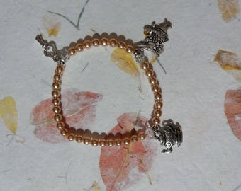 """Young girl pink and charm bracelet """"Alice in Wonderland of"""" rabbit, teapot, key"""