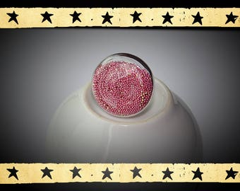 a round and flattened sandblasted pink and gold filled glass globe mounted on a ring holder