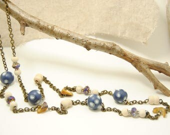 Necklace on bronze chain and blue-white-Tan-coloured beads.