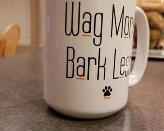 "MUG, ""Wag More, Bark Less."" Coffee cup, tea cup, mug. White with color design. Comes in 11 oz or 15 oz."