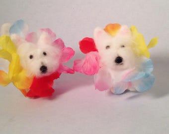 A pair of westies wearing lei's, miniature figurines