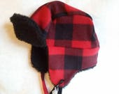 Toddler trapper hat fits up to 18 inches around. Made of fleece and polyester fur lining with fleece ties. Flaps can be worn up or down