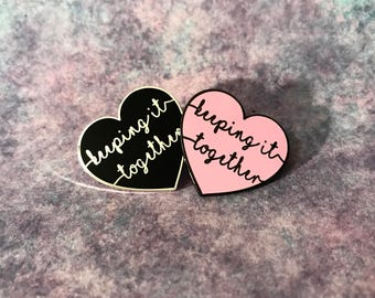 Keeping It Together hard enamel pin. Pink or black.