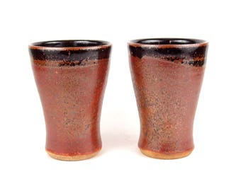 Tumbler cup in textured copper red and shiny black with rust/iron accents