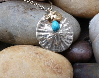 Tidepool Treasures Necklace shows a large silver sanddollar, a gold starfish and scallop shell with a turquoise drop; all on silver chain.