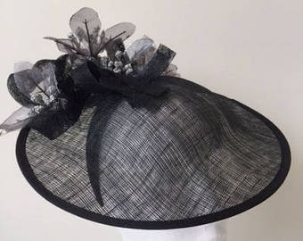 Beautiful black hatinator with sinamay loops, silver flowers on a headband