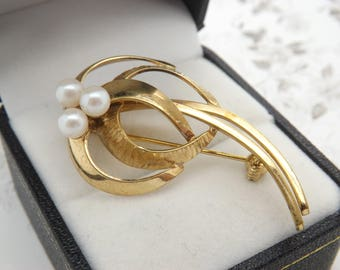 A very fine A+D style abstract flower design vintage jewelry brooch made in an openwork chased and polished rolled gold metal & faux pearls
