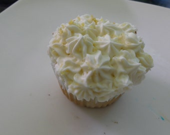 White cake flavored cupcakes filled with vanilla pudding frosted with lemon frosting and garnished with fresh lemon zest/slice
