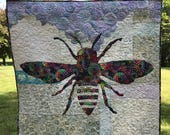 Phoebee is a quilt pattern which uses both sides of one focus fabric for the bee, flowers, and binding on a scrappy background.