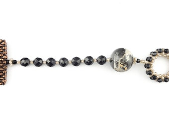 Bracelet with T-bar closure with glossy black and brown crystals and one large Portoro marble sphere