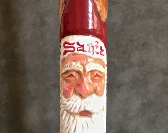 """Hand carved Santa, carved into a 9"""" antique bobbin and hand painted"""
