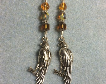 Silver falcon charm earrings adorned with amber Czech glass beads.