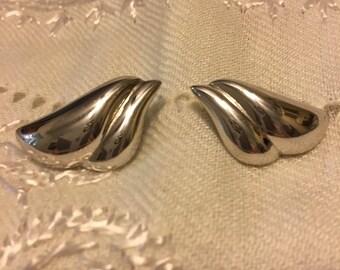 Monet Silvertone stud earrings. Stylish curves.
