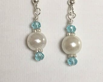 White pearl dangle earrings white pearl drop earrings with turquoise crystals silver embellishment on silver ear wires.