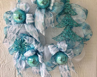Teal and white christmas wreath with snowflakes christmas trees and snowcovered translucent teal christmas ornaments