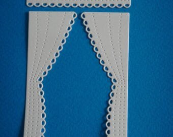 A pair of cutout white curtains for scrapbooking and card