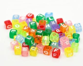 100 cubes are multicolored transparent 6 mm with white letters
