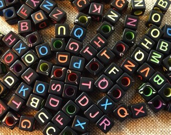 100 multicolored letters on 6 mm black cube beads