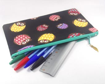 Pouch, flat white on the inside and patterns owls on a black background on the outside with small charm at closure