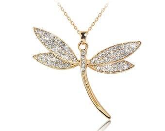 Trés jolie pendentif libellule doré et strass blanc, chaine doré.