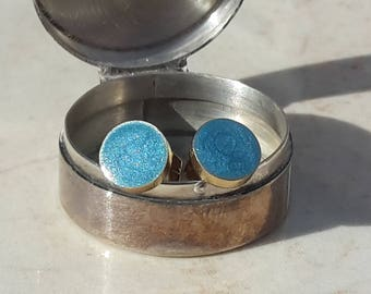 Silver or gold circular stud earrings with light blue colour accent