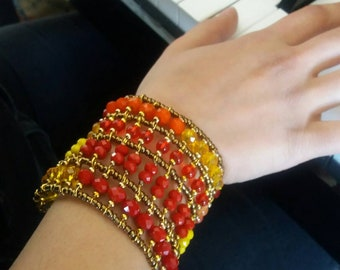 AILÈ Bracelet A band of warm colored beads ranging from red, orange and yellow.