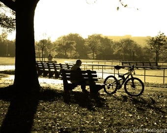 Man with Bike reading in the Park