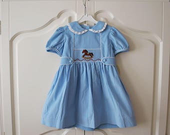Little English girl's smocked dress with rocking horse