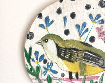 Little round circular painting on reclaimed wood of a greenfinch