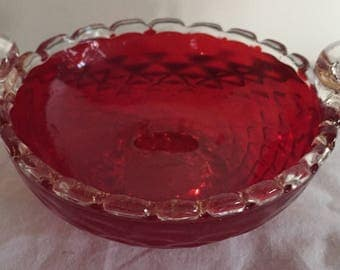 An antique hand made  textured red glass bowl with clear handles and base.