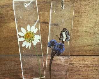 Preserved Daisy; Preserved Butterfly and Forget-me-nots enclosed within a clear casted rectangular Necklace Pendant