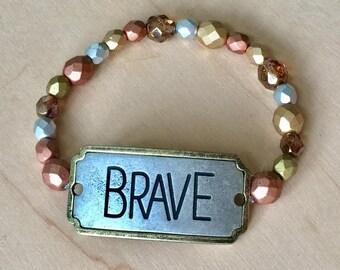 One of a kind, handmade metallic beaded bracelet with metal BRAVE plate