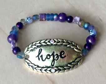 "One of a kind, handmade purple beaded bracelet with gold metal ""hope"" plate"