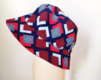 Reversible bucket hat. Red with white polka dot and red and blue geometic print.