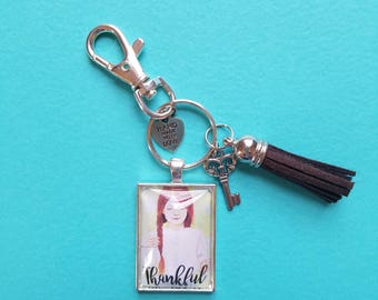 Thankful Pendant Keychain of wearble inspirational art print from original whimsical drawing of a redhead girl with braids. Gratitude gift.