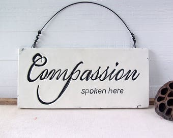 Compassion Spoken Here.  Fired Ceramic Wall Sign.  With Black Letters.