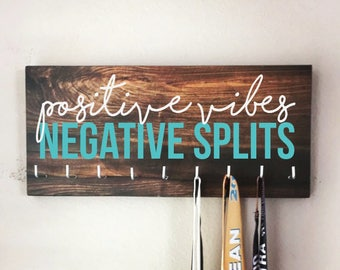 "Race Medal Holder - ""Positive VIBES, Negative SPLITS"" white and teal with wood grain background - 16"" wide"