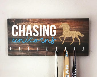 "Race Medal Holder - ""CHASING unicorns"" white and blue with wood grain background - 16"" wide"