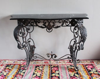 Decorative baroque dark marble topped console, distressed metal.