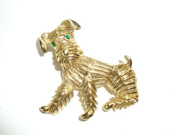 """Gerrys Gold Tone Scotty Dog Brooch marked Gerrys. Vintage gold tone brooch with green stone eyes is about 2"""" long in good used condition."""