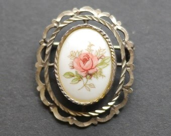 Vintage porcelain brooch, white background with pink rose in ornate silver tone surround