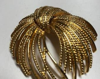 Monet gold tone brooch.