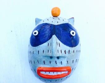 Blue bandit cat w/orange clay wall sculpture