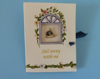 "Pin, Lapel Pin, Brooch depicting a tiny sail boat and statement ""Sail away with me""."
