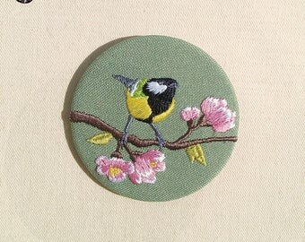 Brooch tit on flowered tree branch
