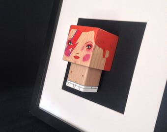 "Figurine ""David Bowie Aladdin Sane"" encadrée ."