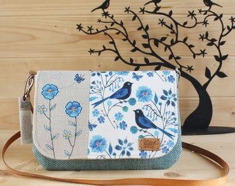 Romantic and delicate wrist wearing handbag or shoulder bag. Flap decorated with applications in free motion and hand embroidery